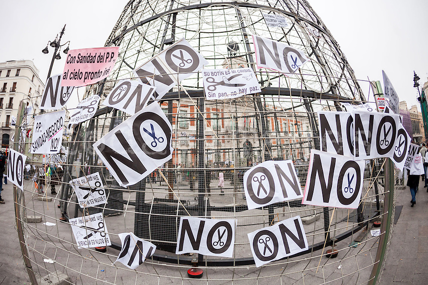 The Christmas Tree of Sol Square during Spanish protest against health privatization with banners