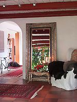 The flower room is comfortably furnished with a large mirror bought in Denmark, which reflects the green of the garden