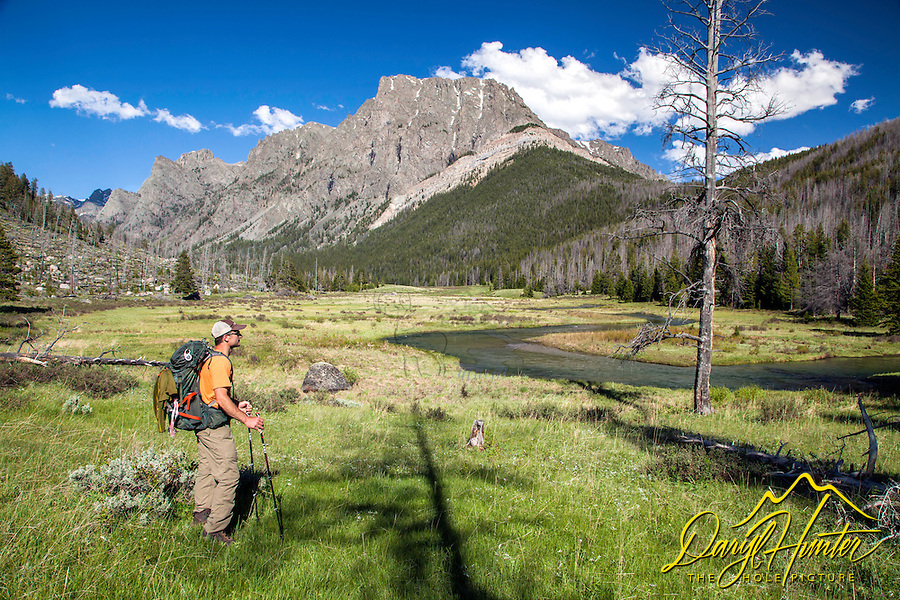 Hiker taking in the scenery of Flat Top Mountain and Clear Creek high in the Wind River Mountains of Wyoming