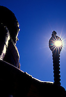 A carved statue of Hawaiian royalty at the Lahaina Center, with the sun peering through the top of the staff.