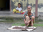 Saridia Waruwu dries cacao in front of her home in Tugala, a village on the Indonesian island of Nias, as her grandson Jesta, age 4, does his homework behind her.<br /> <br /> The village was struck by both a 2004 tsunami and a 2005 earthquake, leaving houses destroyed and lives disrupted. The ACT Alliance helped villagers here to construct new homes and latrines, build a potable water system, open a clinic and schools and get their lives going once again. For the residents of Tugala, the post-disaster mantra of &quot;build back better&quot; became a reality with help from the ACT Alliance.