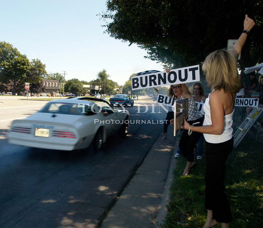 "The Williams sisters, Kristy (center), from Metamora, Mich. hold up large ""Burnout"" signs to try to entice cruisers on Woodward Ave. to stop in front of them and burn rubber, during the 10th Anniversary Woodward Dream Cruise, on Saturday, August 21, 2004, in Pontiac, MI. (Photo by TONY DING)."