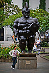 """A  man lies on a statue of the painter and sculptor Fernando Botero, who supervises the assembly of historical work """"Via Crucis, Passion of the Christ """" at the Museum of Antioquia in Medellin, Colombia. 01/04/2012. Photo by Fredy Amariles / VIEWpress."""