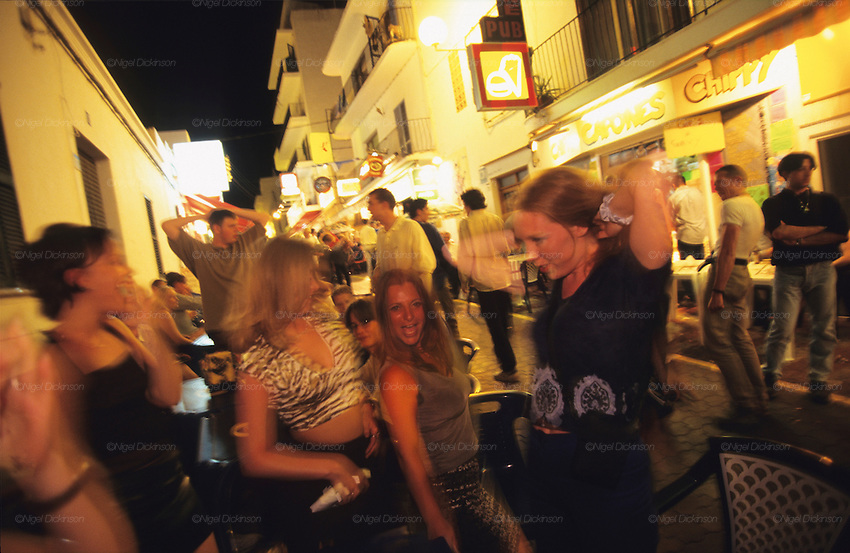 TOURISM CLUBBING, Ibiza.  British tourists on package holidays, San Antonio, Ibiza & Formentera, Baleares islands, Spain, Mediterranean, Europe. Popular holiday resort catering mainly for european tourists. Summer high season, April until September. Well known for 24 hour nightclubbing, package holidays, jet set, all night raves, dancing, techno clubs, drag queens & gay scene, discotheques, speciality theme nights, soapsuds, foam parties, espuma, la mousse. Attractions include shopping, beaches, watersports, boating..