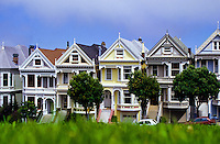 Old colorfull painted wooden victorian style houses and grass in San Francisco, California, USA