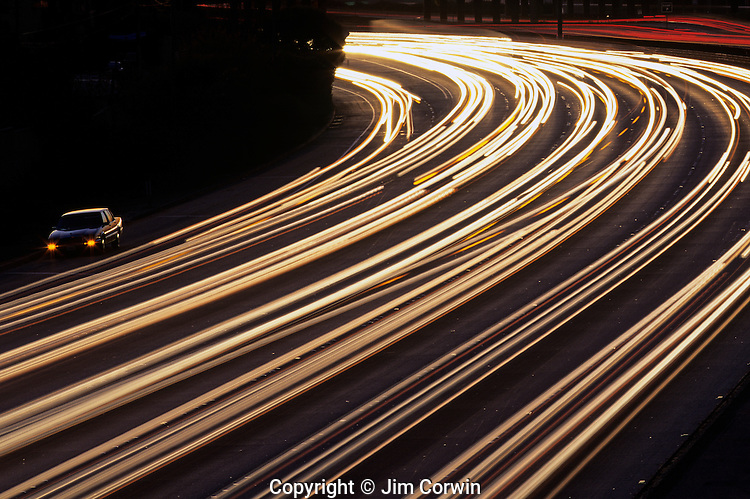 Car broken down on side of highway with car light trails on Highway 10, Los Angeles, California USA.