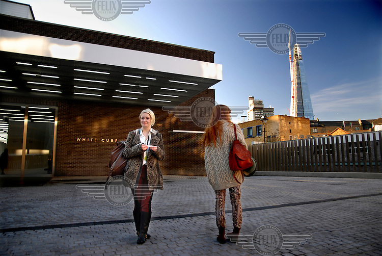 Young women outside the White Cube Art Gallery on Bermondsey Street in London with the Shard in the background.