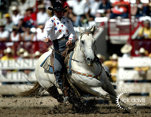 Ladies barrel racing is a popular rodeo sport featured at most western rodeo events. Turning the barrels in the mud of Cheyenne, Wyoming at the Cheyenne Frontier Days Rodeo.