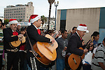 Mexican Mariachi musicians in santa hats participating in the Christmas tradition of Las Posadas in Long Beach, CA