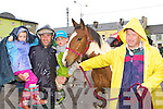 Eileen, Brendan, Tom and Jack O'Connor protecting themselves from the weather at the Killorglin Horse Fair on Saturday