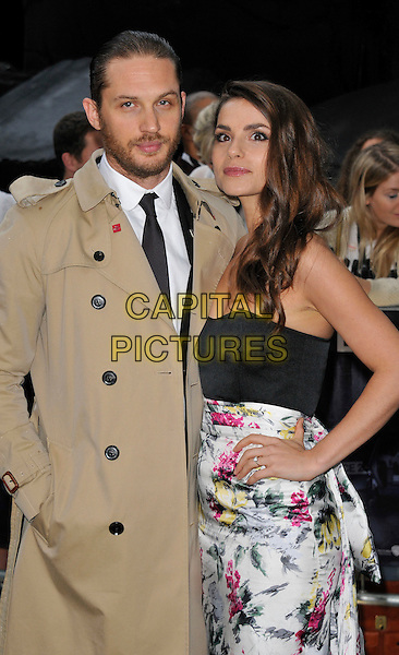 Tom Hardy and Charlotte Riley.'The Dark Knight Rises' European premiere at Odeon Leicester Square cinema, London, England..18th July 2012.half beige trenchcoat length black top strapless white pink yellow floral print couple beard facial hair hand on hip in pocket   .CAP/WIZ.© Wizard/Capital Pictures.