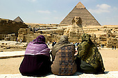 Three Egyptian Women sitting in front of the Sphinx and the pyramids in Giza, Egypt