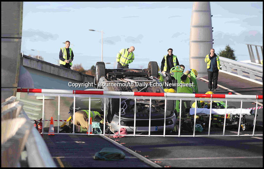 BNPS.co.uk(01202 558833)<br /> Pic: CorinMesser/BNPS<br /> <br /> Fire crews extract the pensioner from her upturned Renault Clio.<br /> <br /> A pensioner had a miracle escape when she crashed her car through a safety barrier and jumped across a gap in a lifting bridge.<br /> <br /> In a scene more reminiscent to an action movie, the 86-year-old woman drove at 20mph through flashing red lights warning motorists the Poole harbour bridge was opening.<br /> <br /> Her silver Renault Clio smashed into the red and white gate and carried on along the road bridge as it was being raised.<br /> <br /> The sudden incline in the surface acted as a ramp and the pensioner's small vehicle shot off the end of the carriageway and plunged 6ft before landing on the other side.<br /> <br /> The car then overturned, trapping the shocked but injured woman inside.