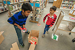 Sohan Vadlakunta, left, and his brother Sathvik Vadlakunta help build an obstacle during the Mini Golf Night at the Carson City Library on Friday May 9, 2014. Kids and parents built a custom mini golf course throughout the library using anything at their disposal and engineering ideas to make a difficult course. Everything from tables to shelves were used to create creative courses.<br />