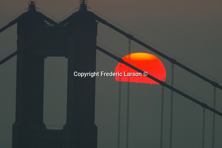 The sun filtered through the thick morning haze framed by Golden Gate Bridge, California.