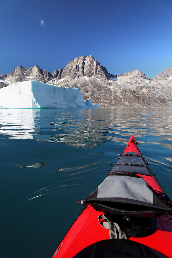 Sea kayaker paddling on Ikaasatsivaq Fjord below mountain and tabular iceberg, Ammassalik Island, East Greenland