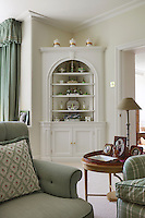 A corner shelving unit in the sitting room displays a collection of green and white china