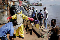 An IFRC Safe and Dignified Burial Team disinfecting themselves before taking off the PPE (personal protection equipment) after collecting the body of fisherman Mohammed Kamara, 52, from the Ferry Terminal community. According to his family he became seriously ill on 3 November and died 3 days later. Test results later confirmed that he had died from ebola.