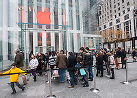 Shoppers line up to enter the Apple Store, with the Apple logo colored red,  on Fifth Avenue in New York during the Christmas shopping season on Saturday, December 1, 2012. (© Richard B. Levine)