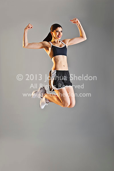 Young Caucasian woman wearing black sports clothing jumping in the air