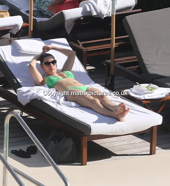 NON EXCLUSIVE PICTURE: MATRIXPICTURES.CO.UK.PLEASE CREDIT ALL USES..UK, AUSTRALIA, NEW ZEALAND AND ASIA RIGHTS ONLY..English model and media personality Kelly Brook is pictured sunbathing poolside in a green bikini in Miami today...FEBRUARY 1st 2013..REF: KDA 13684..XIM