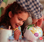 SOUTHBURY, CT 10/10/98  --1010JH01.tif--Samantha Mendez, 5, of Southbury applies some paint as her dad Vince Mendez steadies the pumpkin during a pumpkin painting contest Saturday at the Koenig Art Emporium store in the Southbury Plaza. About 30 kids took part in the event, which was held on the sidewalk in front of the store. JOHN HARVEY staff photo for Lazor story.