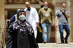 Palestinian women wearing protective mask, walks outside the Ibrahimi mosque, in the midst of the coronavirus COVID-19 outbreak, in the West Bank town of Hebron on June 26, 2020. Photo by Mosab Shawer