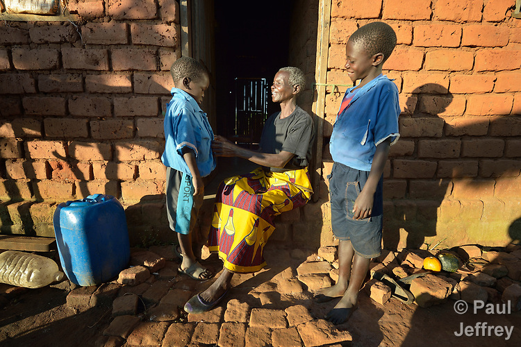 A woman assures her children are properly dressed before they go to school in Kaluhoro, Malawi. With support from the Ekwendeni Hospital AIDS Program, she and other villagers participate in a Building Sustainable Livelihoods program, working together to earn and save money, raise more nutritious food, and receive vocational training.