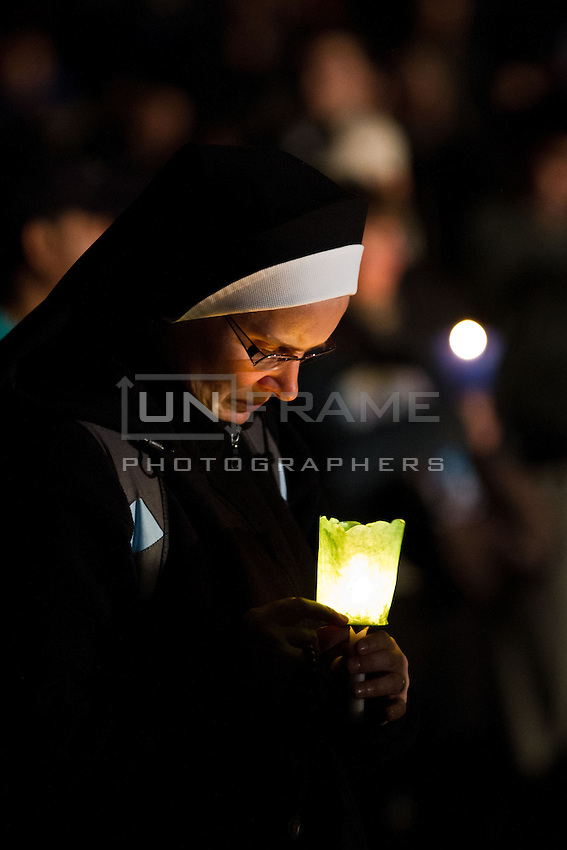 A nun holds a candle during an evening vigil ahead of the beatification of Pope John Paul ll.