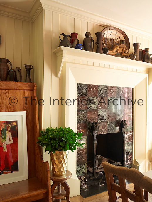 An impressive chequered marble fire surround with Arts and Crafts fire dogs contrasts with the simplicity of the tongue and groove wall covering in the kitchen