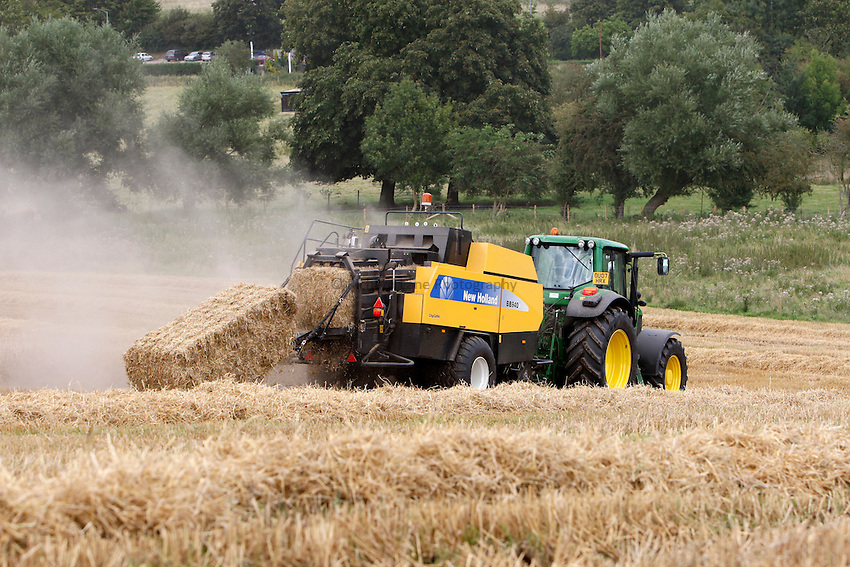 Photo: Richard Lane/Richard Lane Photography. Grain harvest near Amersham, Buckinghamshire. 17/08/2008. A John Deere tractor and New Holland big square baler in spring barley.