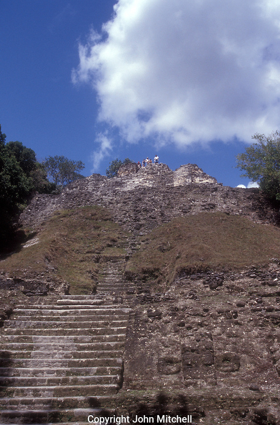 Tourists on top of the tallest structure at the Mayan ruins of Lamanai, Belize