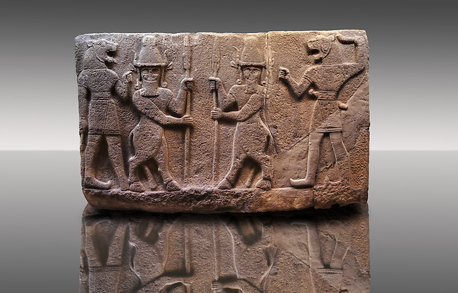 Picture of Neo-Hittite orthostat describing the legend of Gilgamesh from Karkamis,, Turkey. Museum of Anatolian Civilisations, Ankara. Mythological scene. The 2 figures in the center are flanked by lion headed men who have one fist outstretched and are known as Ugallu. The 2 figures in the middle holding spears are men with bodies of bulls known as Kusarikku. 5