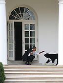 United States President Barack Obama crouches to greet his dog, Bo, outside the Oval Office of the White House, in Washington, DC, Thursday, March 15, 2012..Credit: Martin Simon / Pool via CNP