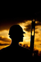 Silhouetted construction worker holding a level.