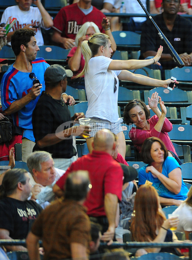 Jun. 15, 2011; Phoenix, AZ, USA; Fans react as the bat of San Francisco Giants batter Bill Hall (not pictured) flies into the crowd in the second inning against the Arizona Diamondbacks at Chase Field. Mandatory Credit: Mark J. Rebilas-