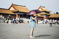 A Chinese woman takes a picture on the pavillion of the Forbidden City in Beijing, China, July 20, 2014.<br /> <br /> Smartphones are an essential tool of Chinese ordinary life. Everywhere in China, people use them to take pictures to share online, to talk and chat, to play videogames, to get access to the mainstream information, to get connected one each other. In the country where the main global social media are forbidden - Facebook, Twitter and Youtube are not available  -, local social networks such as WeChat have a wide spread all over the citizens. The effect is an ordinary and apparently compulsive way to get easy access to digital technology and modern way of communication. <br /> A life through the display. Yes, We Chat.<br /> <br /> © Giorgio Perottino