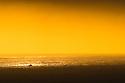 A boat moves north up the California coast along Big Sur..Tripod.No flash.