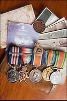 BNPS.co.uk (01202 558833)<br /> Pic: PhilYeomans/BNPS<br /> <br /> Family photos that saved him, Military medal (with bar) as well as the Mons Star,leather wallet, dog tag and his map of the Passchendaele offensive from 1917.<br /> <br /> Saved by pictures of his loving family...<br /> <br /> An amazing tale of a heroes lucky survival through the entire First World War has been uncovered after his family revealed his remarkable tale to a local history group.<br /> <br /> Photos of loved ones that saved a soldier's life by stopping a piece of shrapnel aimed for his heart have come to light - complete with the holes the fragment left behind.<br /> <br /> Private William Taylor kept the nine pictures of his family in his wallet in his breast pocket during the entire four years of World War One.<br /> <br /> In a remarkable quirk of fate he survived a battle which left three quarters of his regiment dead or injured thanks to the stack of photos which took the impact of a shell blast.<br /> <br /> The projectile pierced the outer layer of his leather wallet and perforated eight of the nine photos.<br /> <br /> Luckily, the last picture of his younger sister Lilly stopped the fragment from going any further.