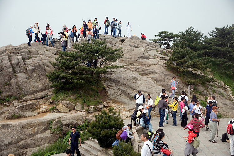 Tourists look at scenery from atop the Bright Summit Peak in the upper reaches of Huang Shan, a popular mountainous tourist destination in Anhui Province, China.  Huang Shan is also known as Yellow Mountain in English.
