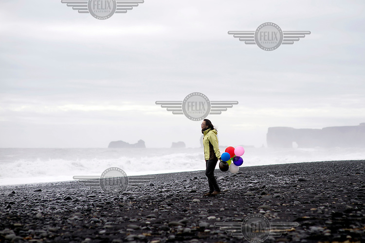 A tourist holding some ballons on Reynisfjara beach. In the background is Dyrholaey ('Door Hole') a sea arch that was formed by an under sea volcanic eruption.