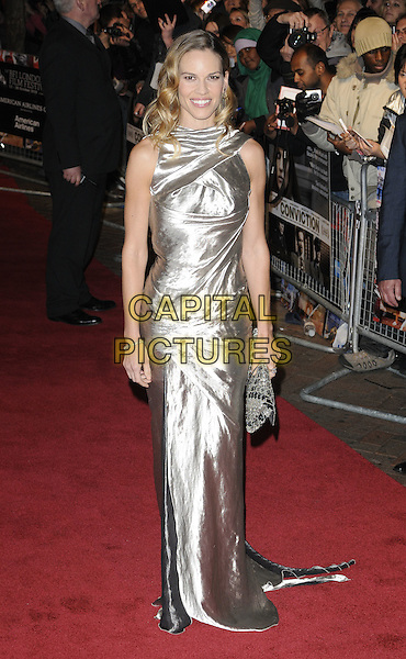 "HILARY SWANK.Attending the 54th BFI London Film Festival screening of ""Conviction"" at Vue cinema, Leicester Square, London, England, UK, October 15th 2010.LFF full length sleeveless  silver shiny metallic wavy hair dress gold long maxi clutch bag smiling .CAP/CAN.©Can Nguyen/Capital Pictures."