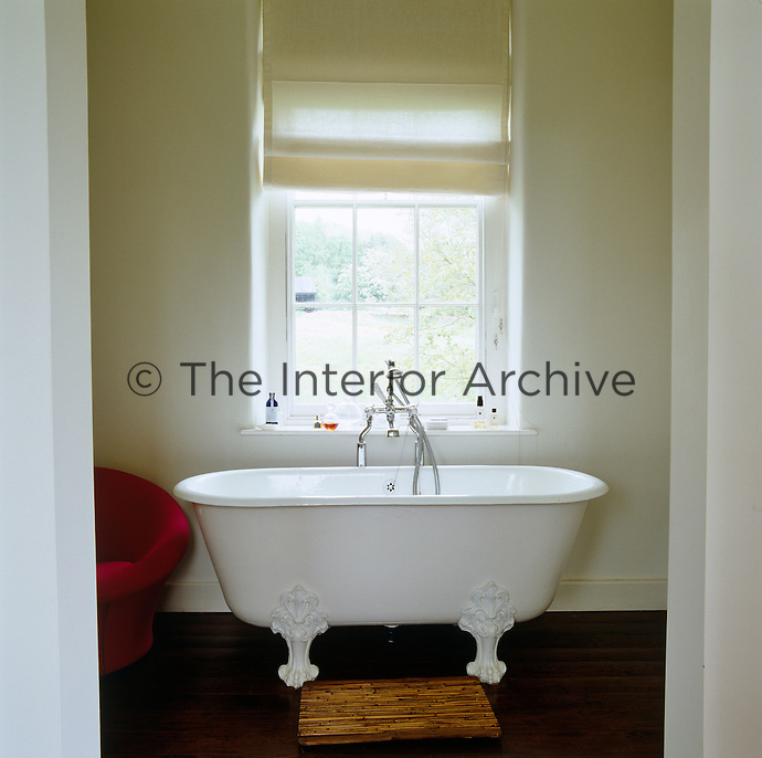 A free-standing roll-top bath with ornamented feet beneath a window in a contemporary bathroom at Bowling Green