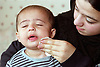 Mother wiping young son's cheek,