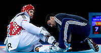 04 DEC 2011 - LONDON, GBR - Aaron Cook (GBR) (on left, in red) receives treatment during his men's -80kg category semi final contest against Nicolas Garcia (ESP) (on right, in blue) at the London International Taekwondo Invitational and 2012 Olympic Games test event at the ExCel Exhibition Centre in London, Great Britain .(PHOTO (C) NIGEL FARROW)