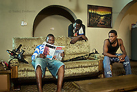 Film director Ola Orlando Shoyinka (center) and crew members rest between shoots on the set of a Nollywood movie production.