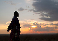 Maasai tribesman looking out over African plains at sunset near Amboseli National Park, Rift Valley Province, Kenya