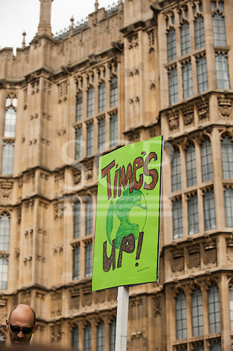 A demonstrator holds a placard which says 'Time's Up!' as he marches in front of the Houses of Parliament during the Climate Change demonstration, London, 21st September 2014. © Sue Cunningham