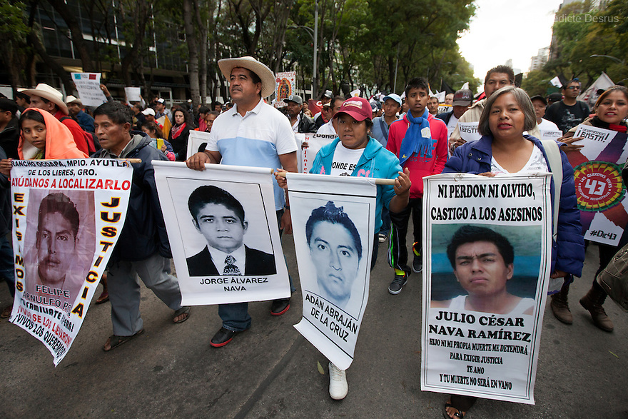 Parents and relatives of the missing students from Ayotzinapa's teacher training college, hold images of the missing students during a march to mark the three months since the disappearance of 43 Ayotzinapa's teaching college students in Mexico City on December 26, 2014. The 43 students went missing on Sept. 26 after confrontations in which police gunfire killed six people and wounded at least 25 in Iguala, in Guerrero state. Alexander Mora Venancio, one of the 43 missing students of Ayotzinapa, has been identified and confirmed dead by authorities.  Many are demanding justice and that the search for the 42 missing students continue until there is concrete evidence to the contrary. Mexico – officially - lists more than 20 thousand people as having gone missing since the start of the country's drug war in 2006, and the search for the missing students has turned up other, unrelated mass graves. (Photo by Benedicte Desrus)
