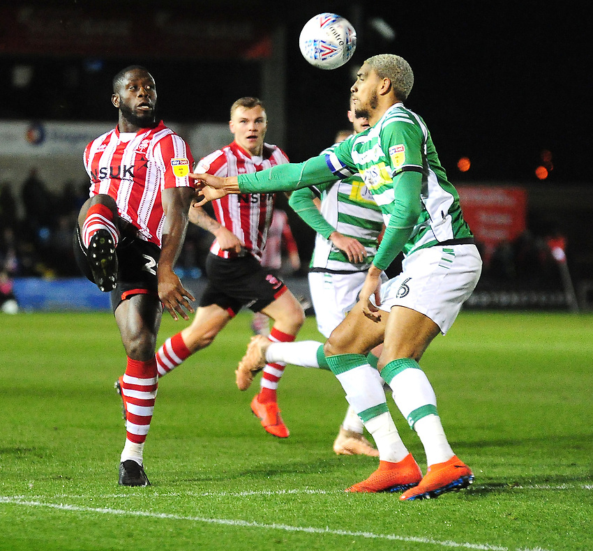 Lincoln City's John Akinde lifts the ball over Yeovil Town's Omar Sowunmi<br /> <br /> Photographer Andrew Vaughan/CameraSport<br /> <br /> The EFL Sky Bet League Two - Lincoln City v Yeovil Town - Friday 8th March 2019 - Sincil Bank - Lincoln<br /> <br /> World Copyright © 2019 CameraSport. All rights reserved. 43 Linden Ave. Countesthorpe. Leicester. England. LE8 5PG - Tel: +44 (0) 116 277 4147 - admin@camerasport.com - www.camerasport.com